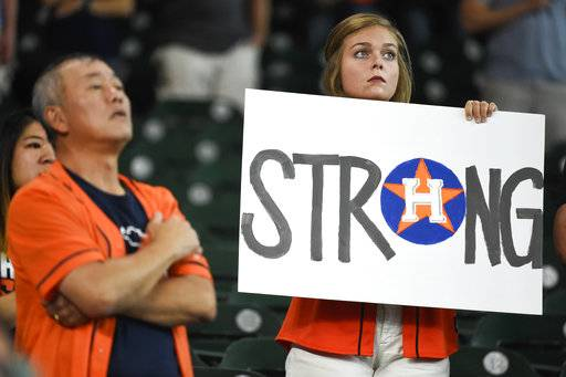 A fan holds a sign during the national anthem before the first game of a baseball doubleheader against the New York Mets, Saturday, Sept. 2, 2017, in Houston. (AP Photo/Eric Christian Smith)