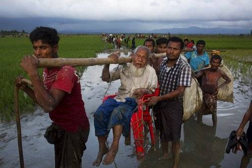 Ethnic Rohingya carry an elderly man and walk through rice fields after crossing over to the Bangladesh side of the border near Cox's Bazar's Teknaf area, Friday, Sept. 1, 2017. Myanmar's military says almost 400 people have died in recent violence in the western state of Rakhine triggered by attacks on security forces by insurgents from the Rohingya. Advocates for the Rohingya, an oppressed Muslim minority in overwhelmingly Buddhist Myanmar, say hundreds of Rohingya civilians have been killed by security forces. Thousands have fled into neighboring Bangladesh. (AP Photo/Bernat Armangue)