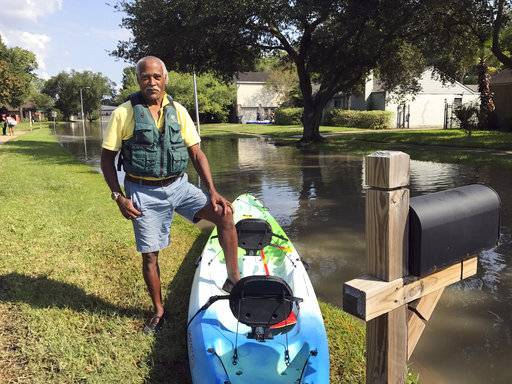 In this Thursday, Aug. 31, 2017 photo, Gordon Prendergast poses with the kayak he bought to see how his house in Houston's western neighborhoods fared after Harvey caused flooding in land that not long ago had been open prairie. Tens of thousands of homes were inundated when floodwater roared around the edge of Houston's Addicks Dam for the first time in its 70-year history. (AP Photo/Nomaan Merchant)