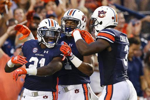 Auburn running back Kerryon Johnson, left, wide receiver Darius Slayton, center, and wide receiver Nate Craig-Myers, right, celebrates Johnson's touchdown in the first half of an NCAA college football game against Georgia Southern, Saturday, Sept. 2, 2017, in Auburn, Ala. (AP Photo/Brynn Anderson)