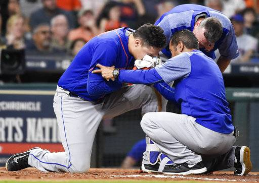 New York Mets' Wilmer Flores, left, is looked at by trainers after fouling a pitch off his face during the fourth inning of the second game of a baseball doubleheader against the Houston Astros, Saturday, Sept. 2, 2017, in Houston. Flores left the game and was replaced by Amed Rosario. (AP Photo/Eric Christian Smith)