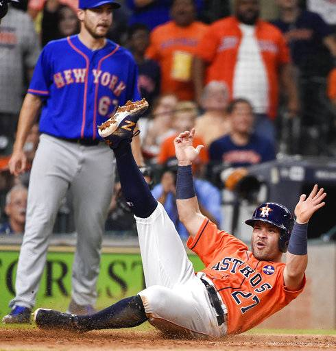 Houston Astros' Jose Altuve slides safely to score on Marwin Gonzalez's single, as New York Mets starting pitcher Seth Lugo, back left, watches during the sixth inning of the second game of a baseball doubleheader against the New York Mets, Saturday, Sept. 2, 2017, in Houston. (AP Photo/Eric Christian Smith)