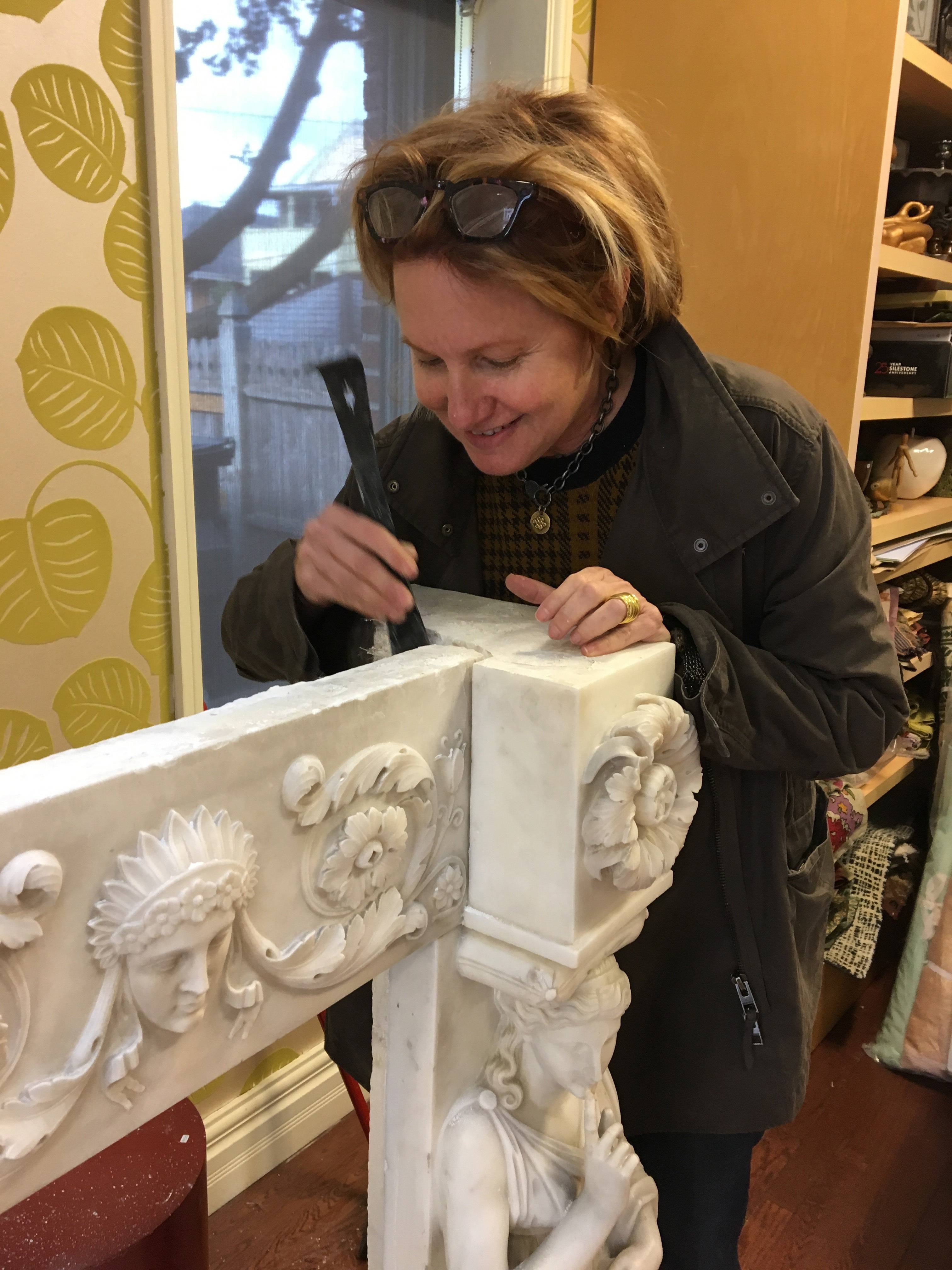 Interior designer Heidi Pribell removes a 1805 marble mantelpiece from the wall of a home in Boston. Pribell sold the mantelpiece to the Museum of Fine Arts later. When Pribell first spotted this dust-covered mantelpiece, it was in the basement of a client's newly purchased home.
