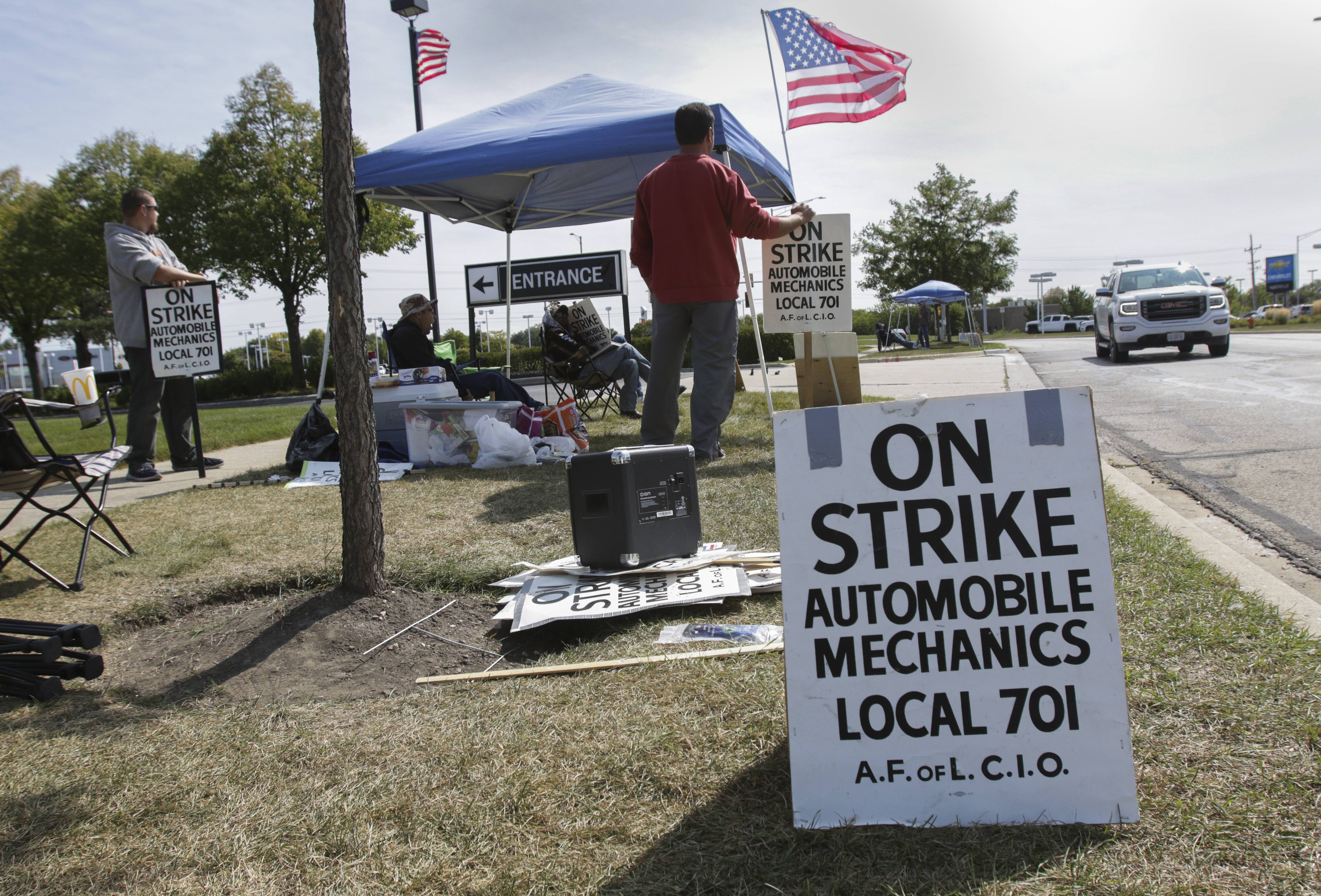 Striking auto mechanics outside Cadillac of Naperville are among hundreds in the region picketing dealerships in a labor action that started Aug. 1.