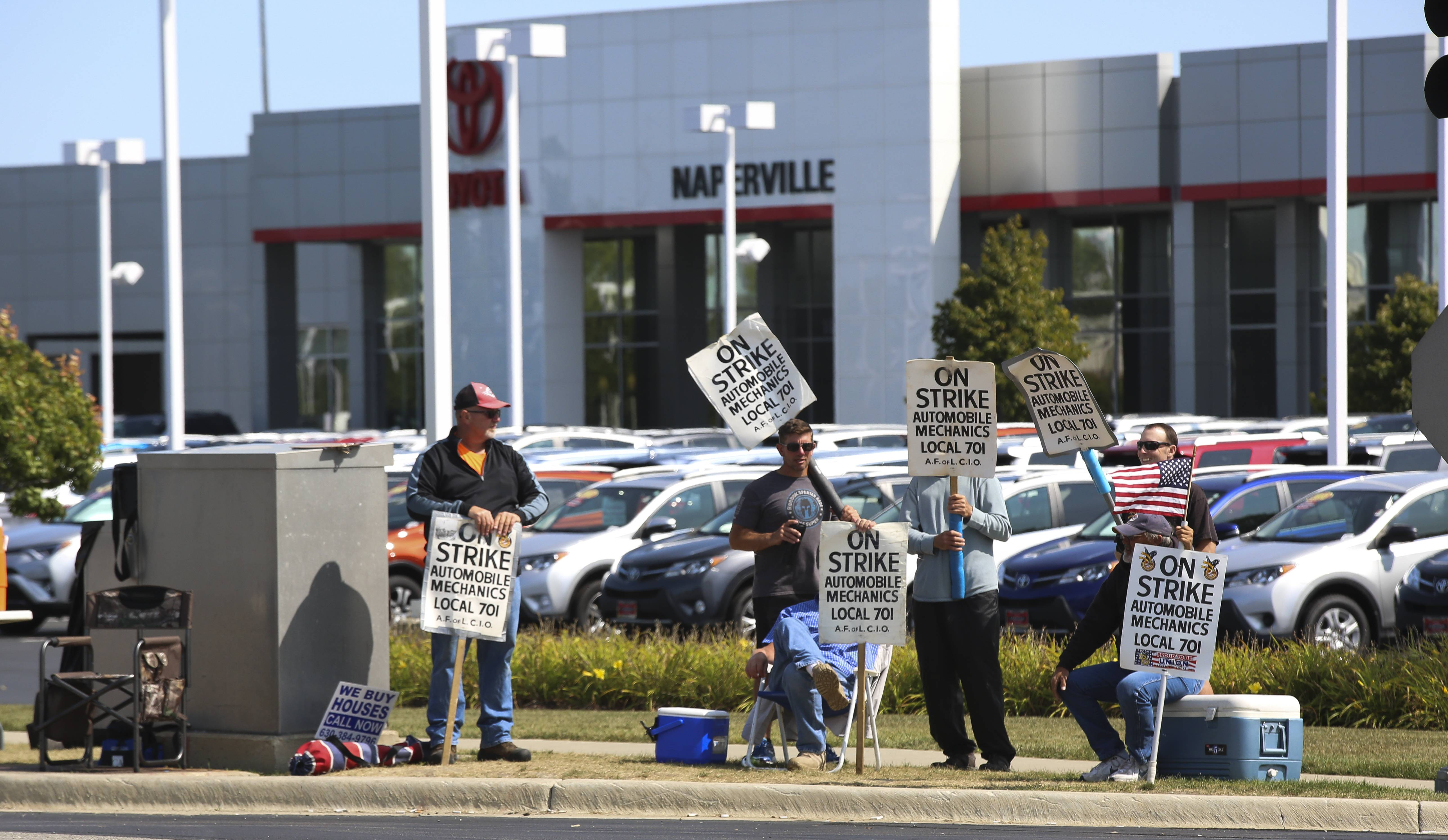 Striking auto mechanics outside of Toyota of Naperville are among hundreds in the region picketing dealerships.
