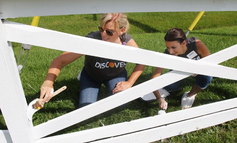 Senior managers Christine Gerasta of Rolling Meadows and Jacklin Lynch of Mundelein paint a fence as part of the Discover Cares service project in Libertyville.