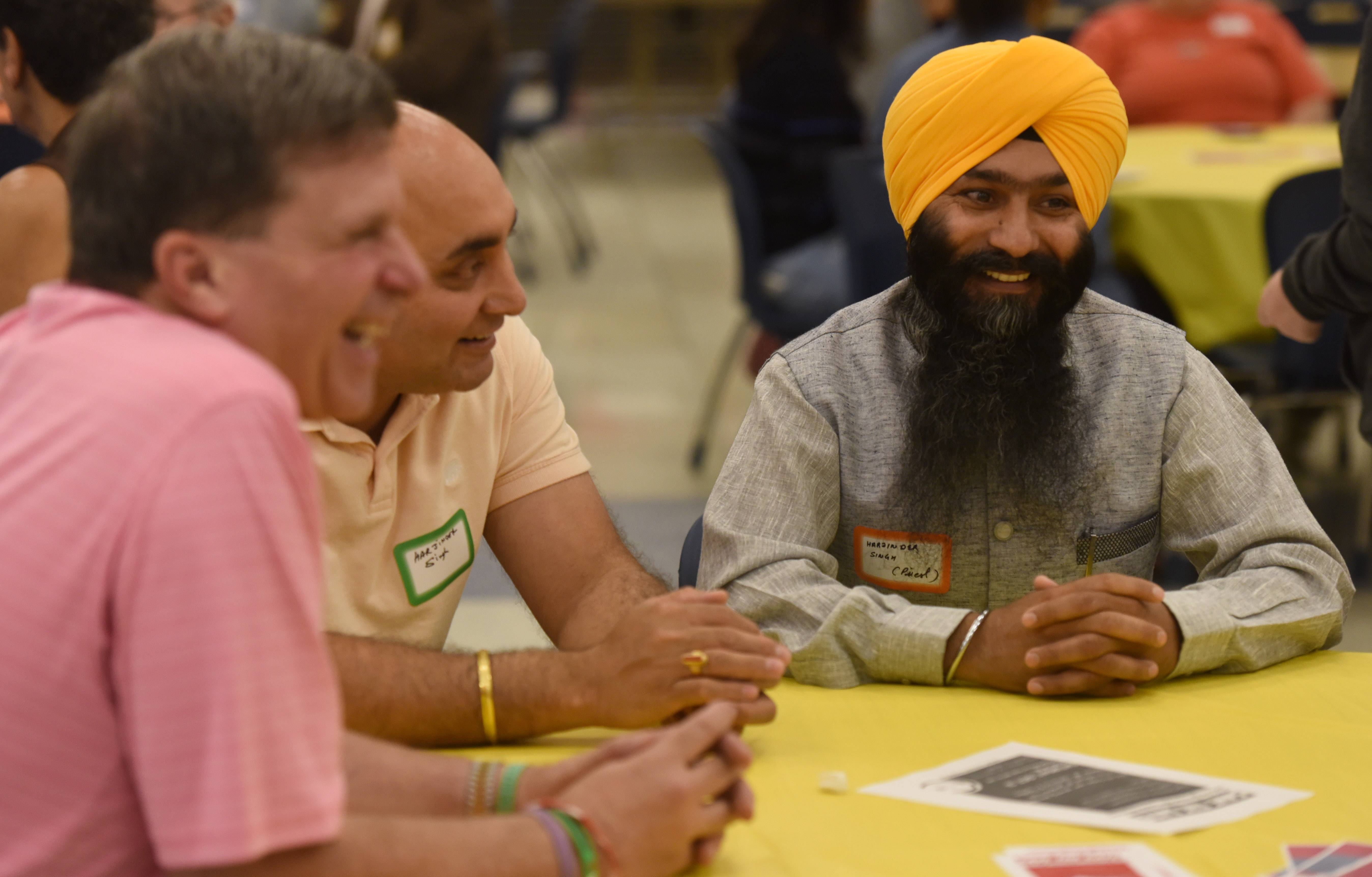 Brett Weiss of Naperville has a conversation with Harjinder (Jindi) Singh and Harjinder Singh, right, who is the priest of the Oak Creek, Wisconsin, Sikh community that was the victim of a white supremacist attack five years ago, during the 6th annual Potluck for Peace at St. Viator High School in Arlington Heights Wednesday.