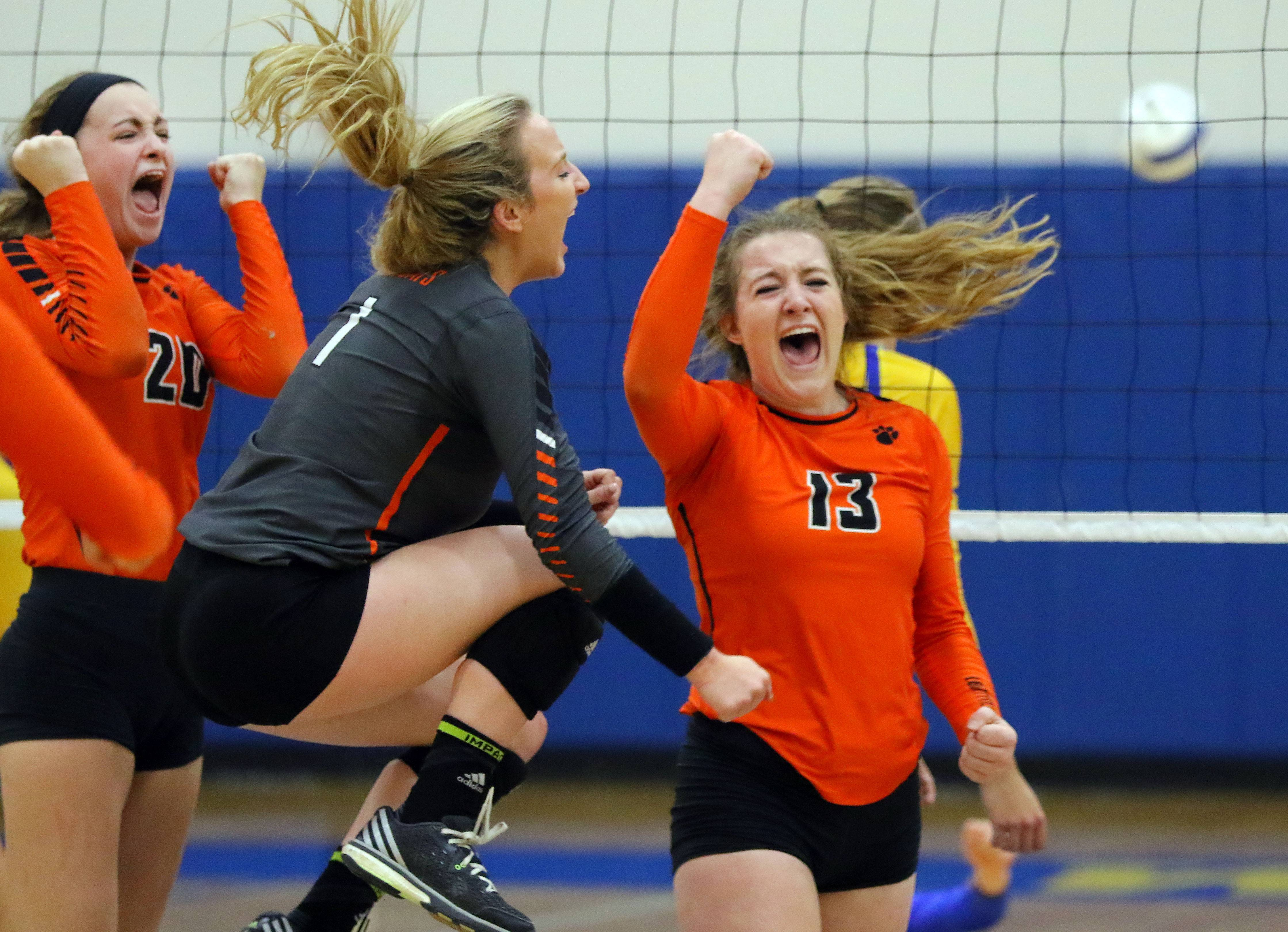 From left, Libertyville's Kellie Hopper, Morgan DeGregor and Amanda Reinhart celebrate after winning the first set Wednesday at Warren.