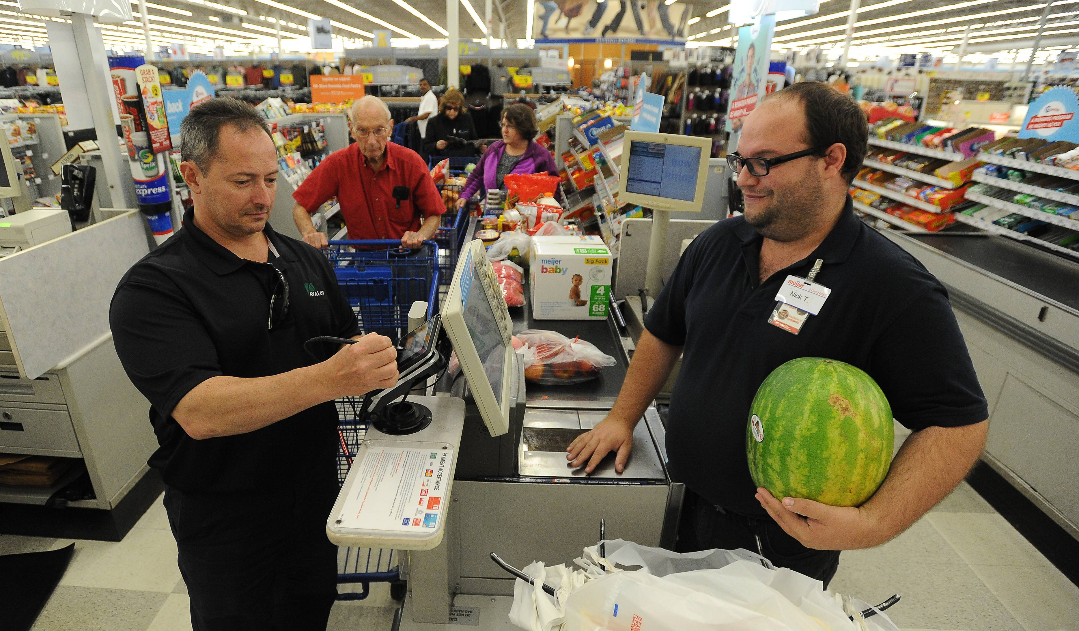 Phil Palmisano of Mount Prospect pays cashier Nick Tihonow of Rolling Meadows for groceries at Meijer in Rolling Meadows. The state will begin taking a cut of local sales taxes beginning this week.