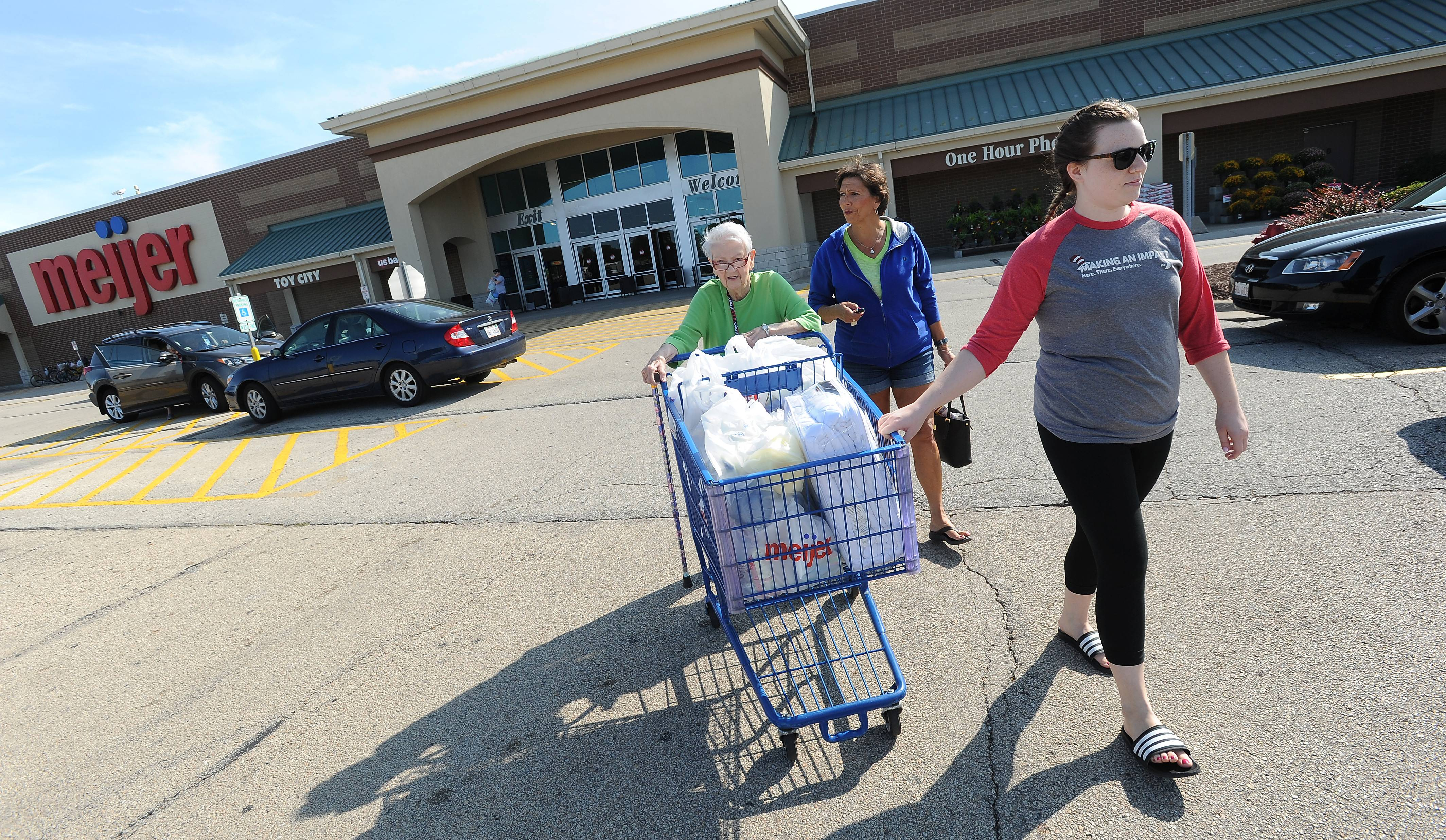 Pam Kaloustian of Arlington Heights, center, and her daughter Stephanie of Chicago help her mother Ellen with shopping at Meijer in Rolling Meadows. The state will begin taking a cut of local sales taxes beginning this week.