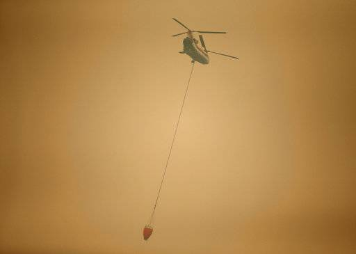 A helicopter with a water bucket flies through dense smoke near Stevenson, Wash., Wednesday, Sept. 6, 2017, as it works to battle the Eagle Creek wildfire on the Oregon side of the Columbia River Gorge. (AP Photo/Randy L. Rasmussen)