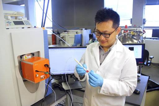 This photo provided by the University of Texas at Austin, shows scientist Jialing Zhang as he demonstrates using the MasSpec Pen to analyze a human tissue sample. Scientists are developing a highly experimental pen-like probe to help surgeons better tell when it's safe to stop cutting or if stray tumor cells still lurk. (University of Texas at Austin via AP)