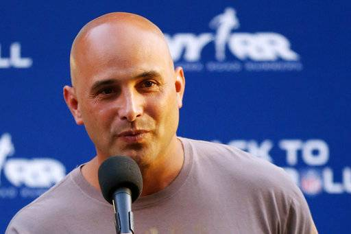 "FILE - In this Aug. 30, 2012, file photo, Craig Carton talks during the National Football League Back to Football Run at Central Park in New York. Federal officials said the New York sports radio host is in custody and details of the charges against the host of WFAN-AM's ""Boomer and Carton� show were not immediately made public Wednesday, Sept. 6, 2017. (John Minchillo/AP Images for NFL, File)"