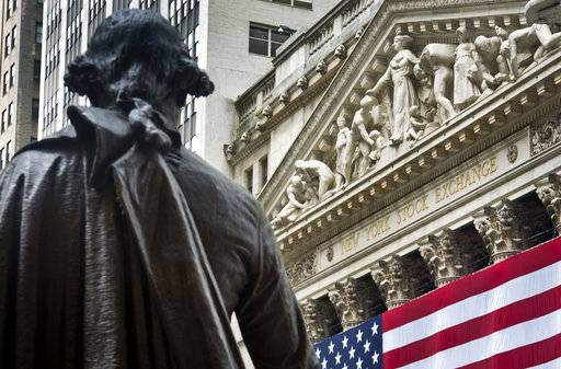FILE - In this Wednesday, July 8, 2015, file photo, Federal Hall's George Washington statue stands near the flag-covered pillars of the New York Stock Exchange. U.S. stocks edged higher in early trading Wednesday, Sept. 6, 2017, recouping some of the market's losses from a day earlier. Banks and energy companies were driving the gains. Airlines, cruise ship operators and travel booking companies were down amid concerns that Hurricane Irma could strike the United States later this week. (AP Photo/Bebeto Matthews, File)