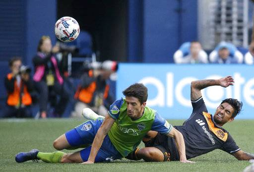 "FILE - In this June 4, 2017, file photo, Seattle Sounders midfielder Alvaro Fernandez, left, and Houston Dynamo defender A. J. DeLaGarza go down as they vied for the ball during an MLS soccer match in Seattle. DeLaGarza posted video of the floodwaters inching toward his home after Hurricane Harvey. ""Another sleepless night. Praying for those already in floods and hoping this rain stops. Much love H-Town,� DeLaGarza wrote. (AP Photo/Ted S. Warren, File)"