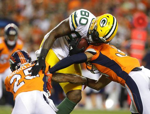 "File- This Aug. 26, 2017, file photo shows Green Bay Packers tight end Martellus Bennett (80) being hit by Denver Broncos cornerback Chris Harris (25) during the first half of an NFL preseason football game, in Denver. So many new veterans for the Green Bay Packers. At their core, the Packers still build through the draft. But general manager Ted Thompson has been more active than usual this season in signing veteran free agents. ""Well, I think you have to realize that any time you acquire a player, whether it's through the draft, free agency, regardless of the time of year, it's a process. It's a process that's always going on,� coach Mike McCarthy said before practice Wednesday, Sept. 6, 2017. (AP Photo/Joe Mahoney, File)"