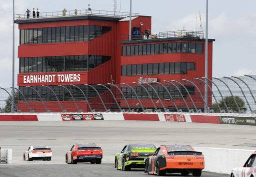 Race cars leave pit road as they drive toward the recently named Earnhardt Towers during qualifying for the NASCAR Xfinity auto race at Darlington Raceway, Saturday, Sept. 2, 2017, in Darlington, S.C. (AP Photo/Terry Renna)