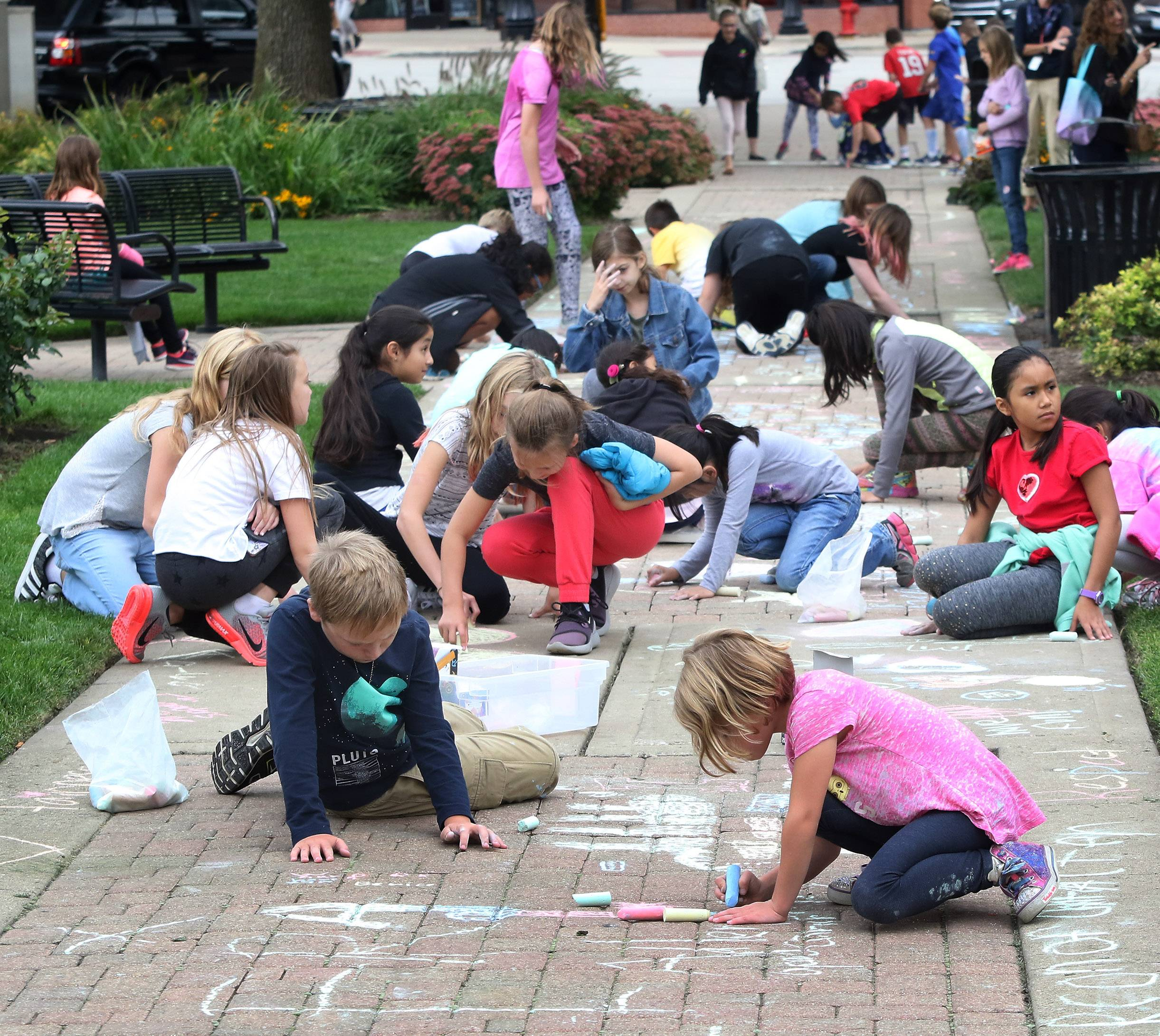 Adler Park School students draw on the sidewalk around Cook Park in Libertyville on Thursday. Libertyville Elementary District 70 fourth- and fifth-graders participated in the Chalk Walk project as part of the national character-building program Character Counts!