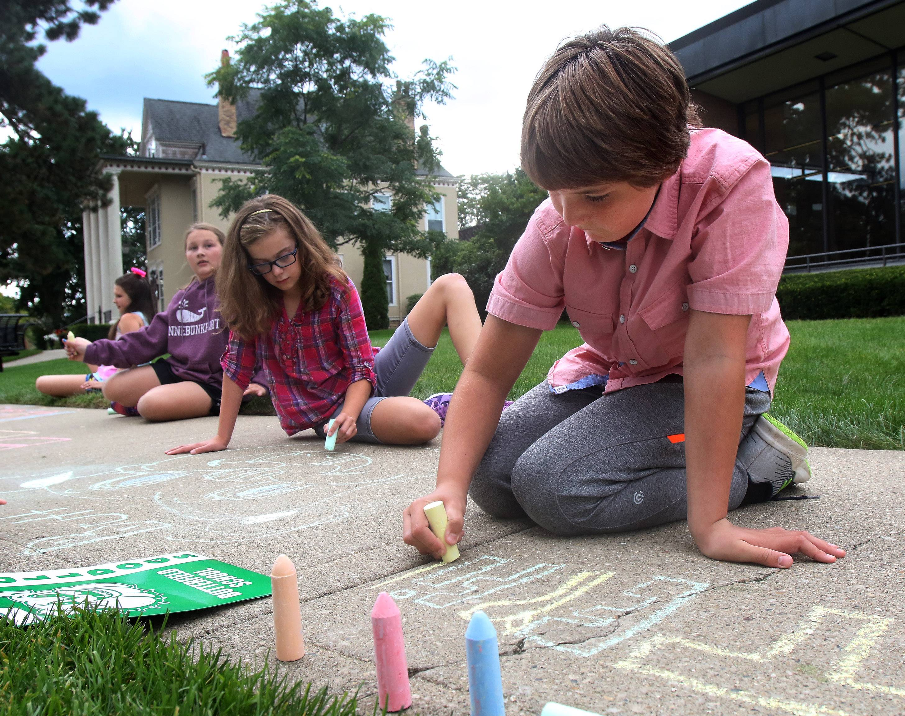 Butterfield School fifth-grade students Katelyn Rein, right, and Olivia Steffensen draw on the sidewalk around Cook Park in Libertyville on Thursday.