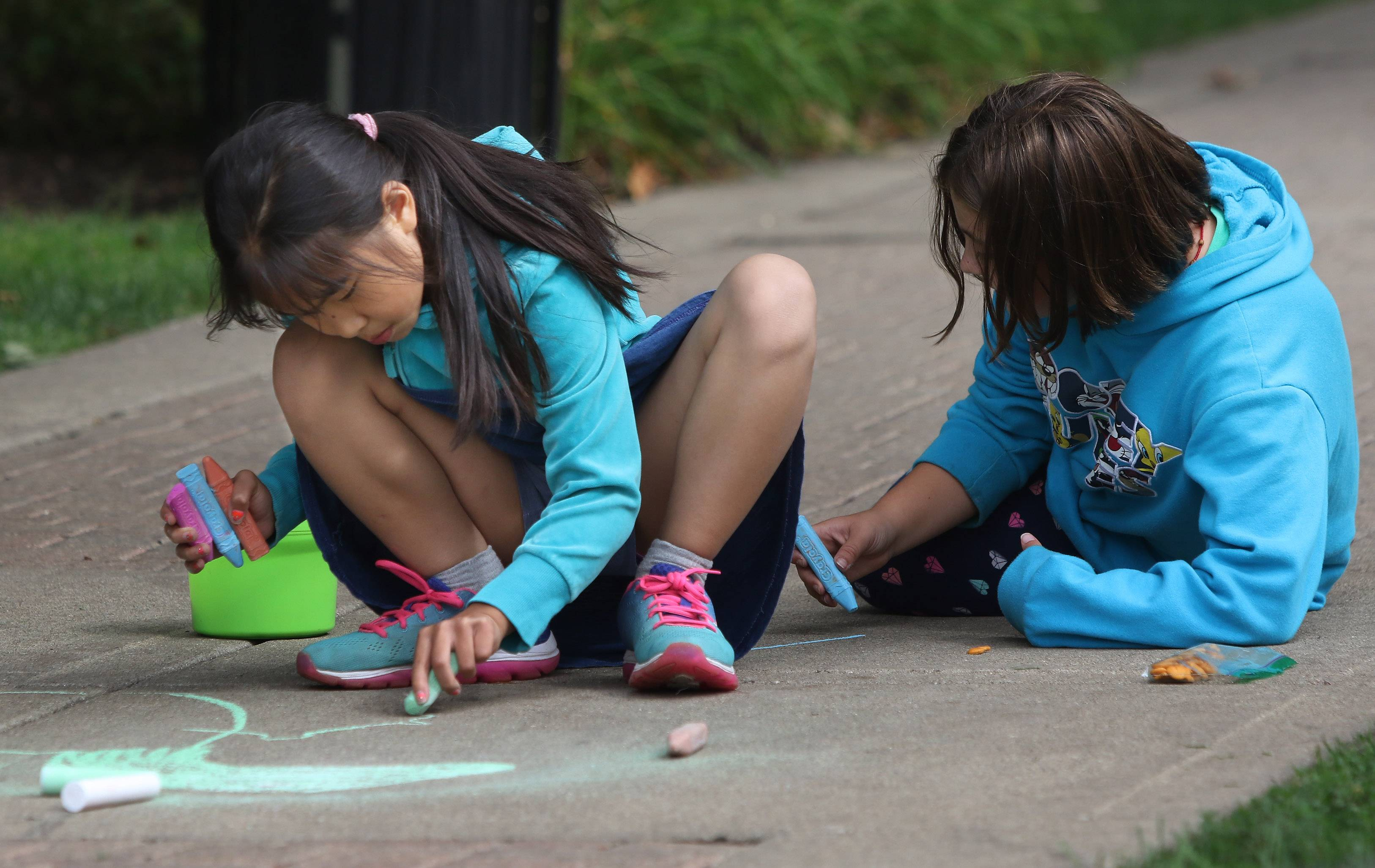 Rockland School fourth-graders Amy Huang, left, and Sorelle Foulke draw on the sidewalk around Cook Park in Libertyville on Thursday. Libertyville Elementary District 70 fourth- and fifth-graders participated in the Chalk Walk project as part of the national character-building program Character Counts!