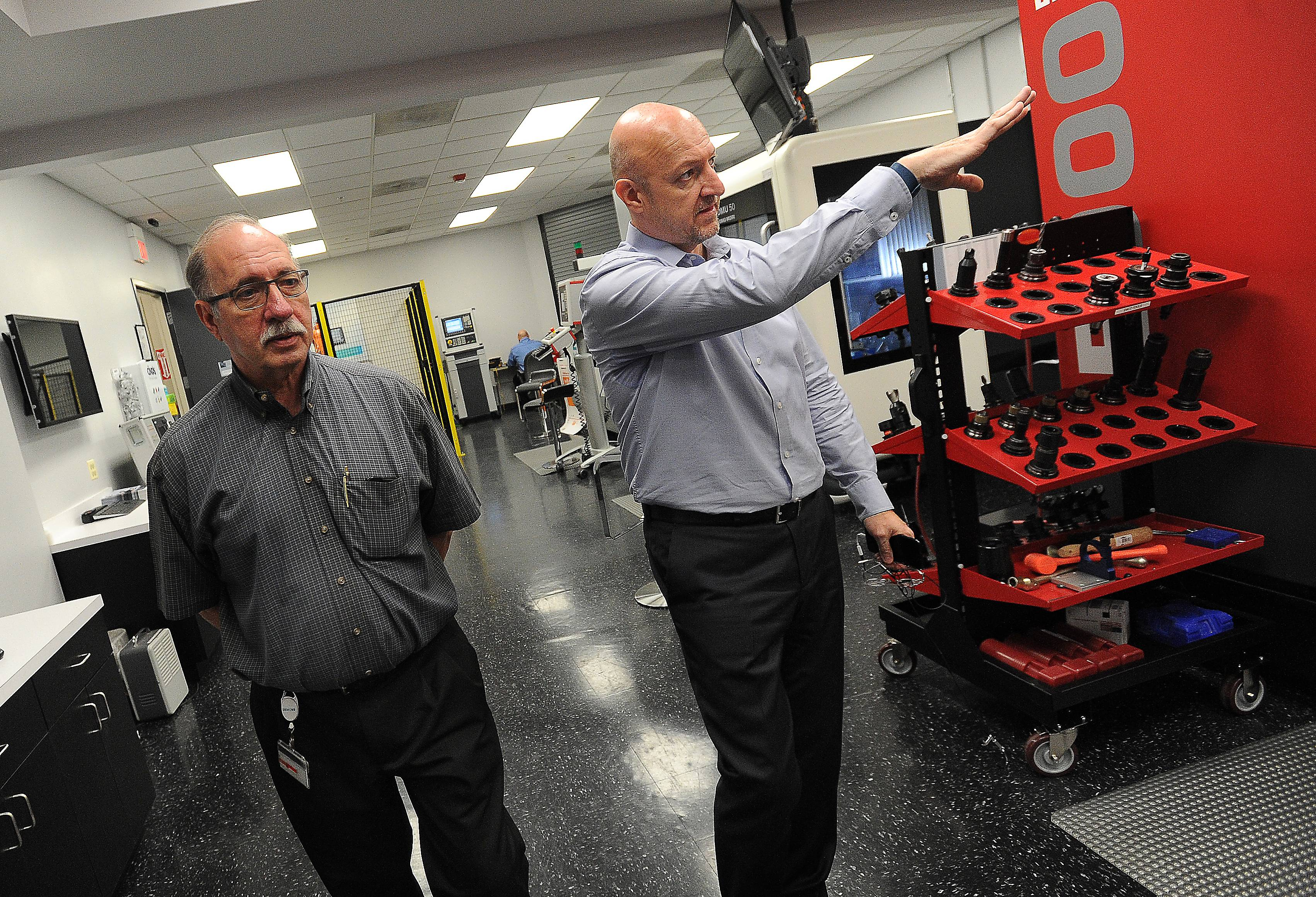 John Meyer, manager of marketing communications and motion control at Siemens, right, along with Randy Pearson, Technical Applications Center manager motion control in Elk Grove Village, shows off the CNC machines at the facility.