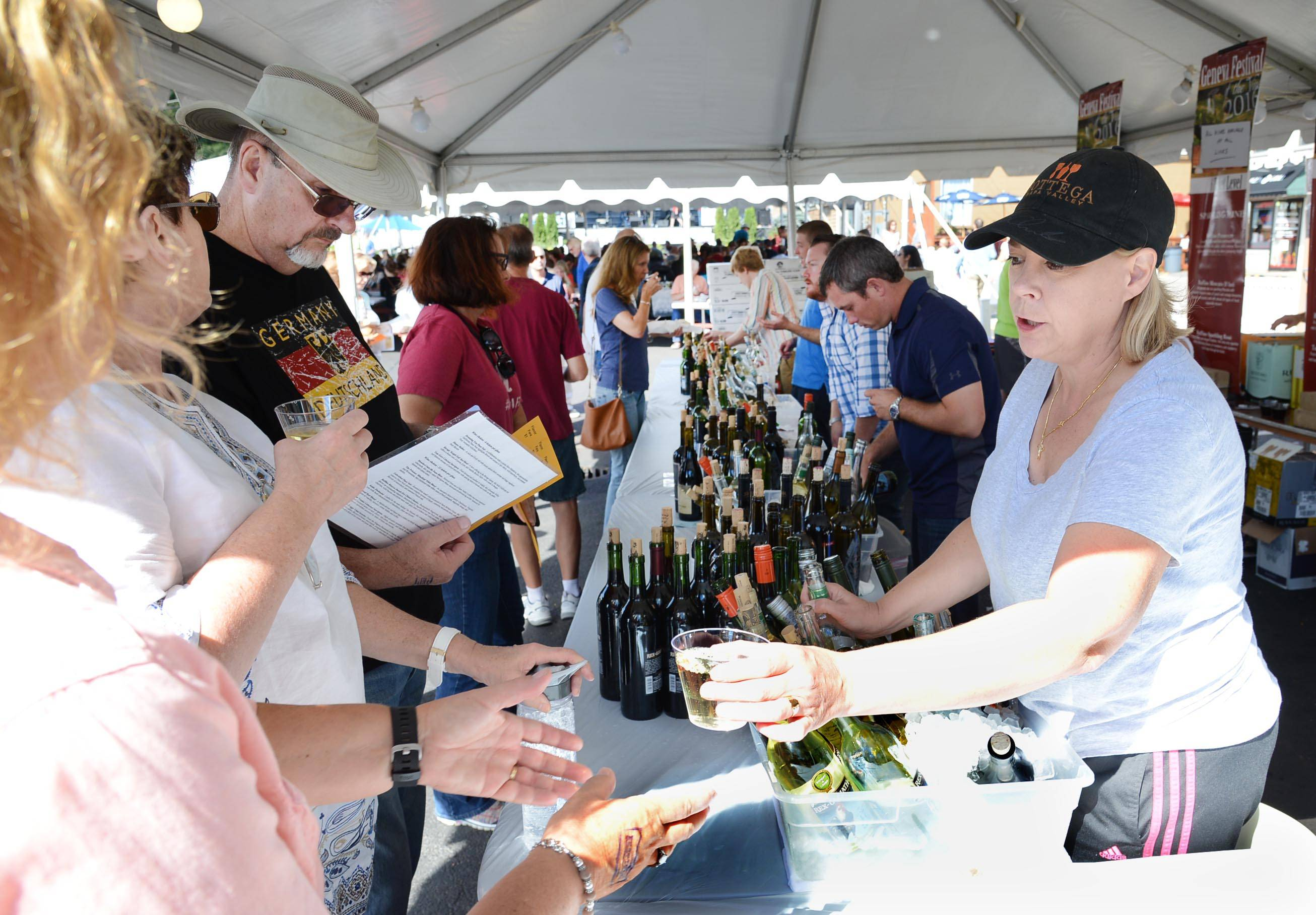 Mary Flynn, of SavWay Fine Wine and Spirits, hands out a sample of riesling during last year's Festival of the Vine in Geneva.