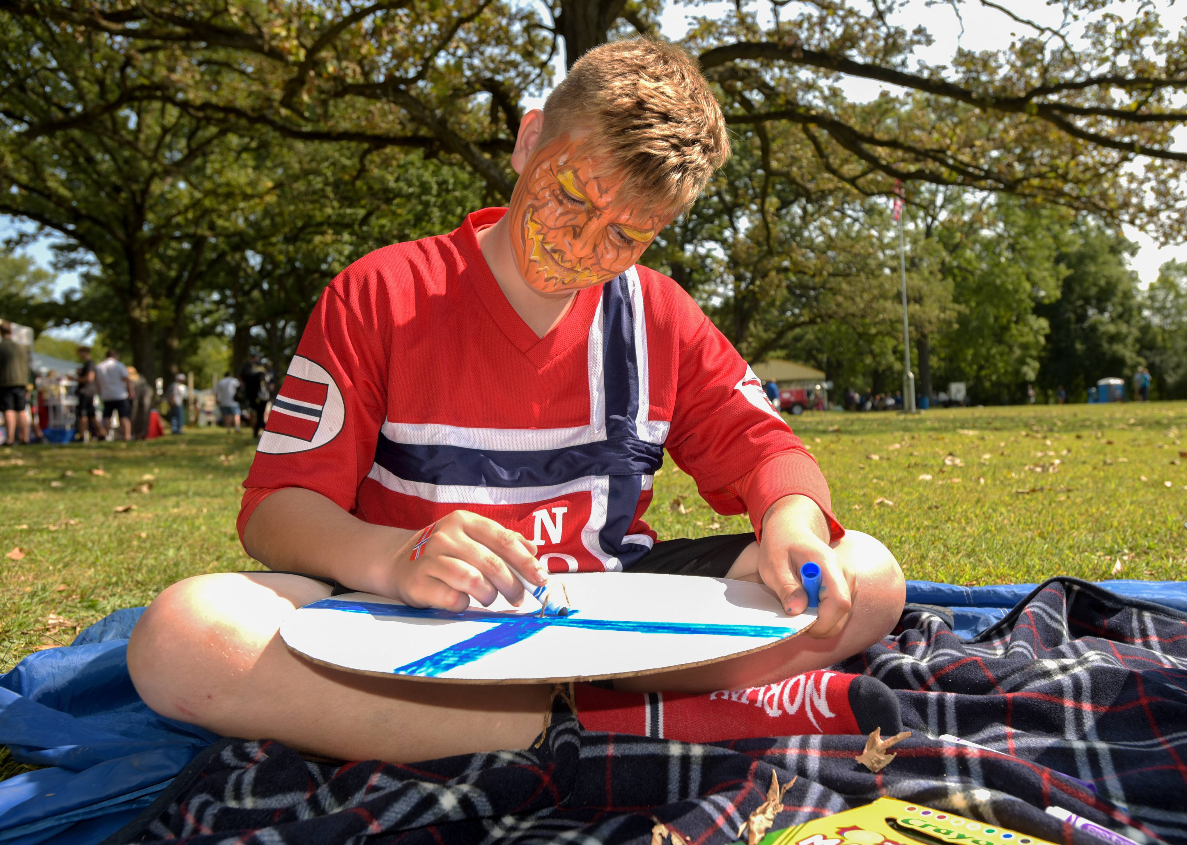 Austin Forney, 12, of Chicago draws a Norwegian flag design on his Viking shield during the 38th Annual Scandinavian Day Festival Sunday in South Elgin.