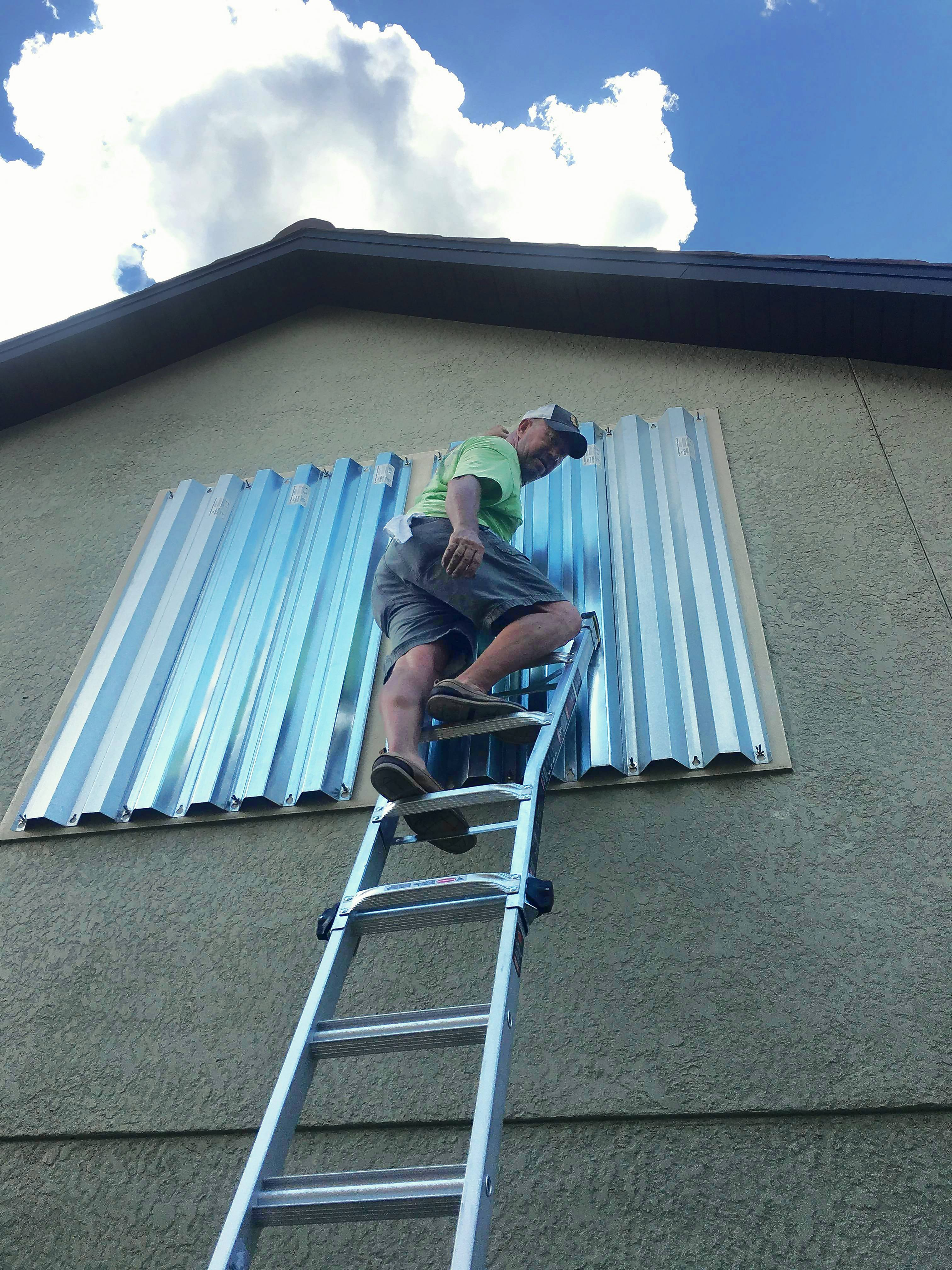 Retired Elk Grove Village police officer Tom Sturgulewski prepares the hurricane shutters of his home in Naples, Florida, where his current law enforcement job is keeping him from evacuating before Hurricane Irma.