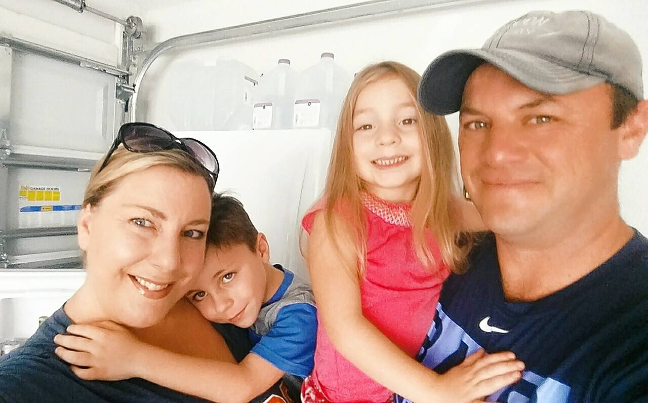 Former Naperville resident Jill (Lakner) McGarry, her 5-year-old son Finnegan, 3-year-old daughter Isla, and husband Josh in front of the garage refrigerator packed with drinking water in their Brandeton, Florida, home.