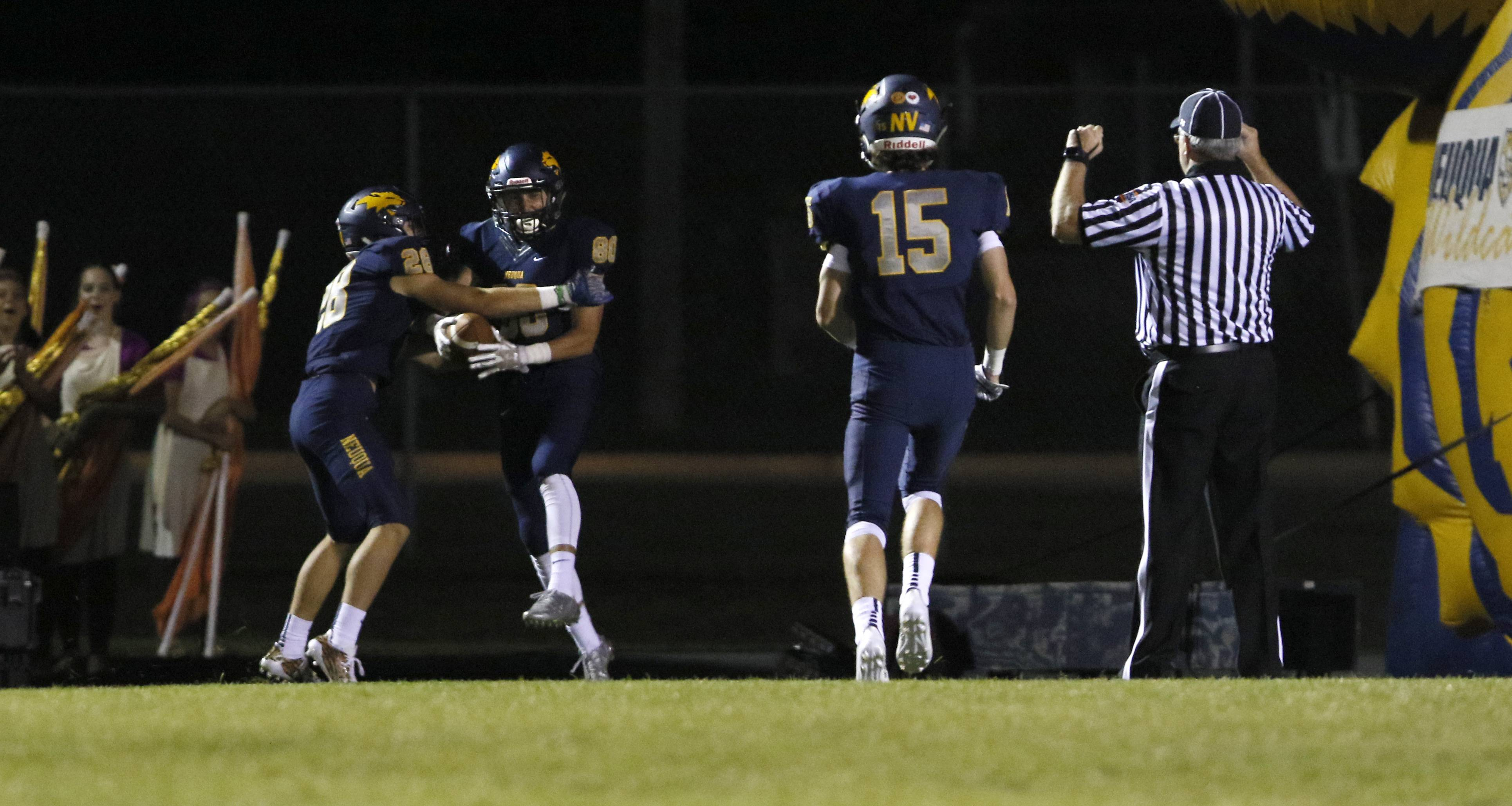 Daniel White/dwhite@dailyherald.comNeuqua Valley's Patrick Hoffman (80) is congratulated by Sean Larkin (28) after scoring on an 88-yard pass play for a 16-0 lead late in the second quarter against Waubonsie Valley. At right is Zach Wenz (15).