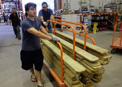 Hanz Paez, left, and Cirous Amiri, right buy wood at a Home Depot in South Miami Dade to secure their property in anticipation of Hurricane Irma early Friday, Sept. 8, 2017 in Miami, Fla. The National Hurricane Center says Hurricane Irma weakened a bit more but remains a powerful threat to Florida.