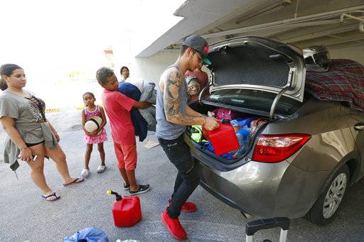 Luis Garcia, right, packs a car that he and five other members of his extended family will use to evacuate north from their home in Miami Beach, Fla, Friday, Sept. 8, 2017.  Cuba evacuated tourists from beachside resorts and Floridians emptied stores of plywood and bottled water after Hurricane Irma left at least 20 people dead and thousands homeless on a devastated string of Caribbean islands and spun toward Florida for what could be a catastrophic blow this weekend.