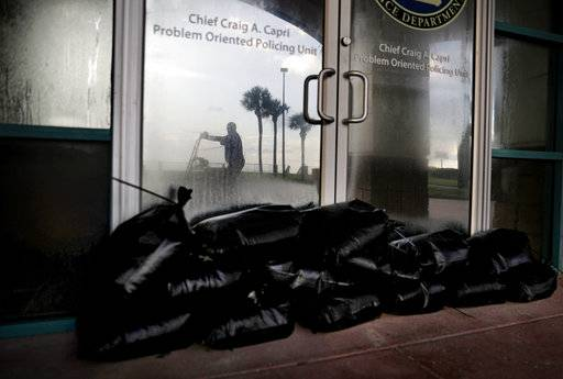 Sandbags sit outside a police station office as a worker secures the grounds of a hotel along the beach ahead of Hurricane Irma in Daytona Beach, Fla., Friday, Sept. 8, 2017. Coastal residents around South Florida have been ordered to evacuate as the killer storm closes in on the peninsula for what could be a catastrophic blow this weekend.