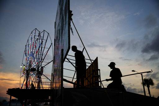 Workers dismantle the facade of a funhouse at an amusement park ahead of Hurricane Irma in Daytona Beach, Fla., Thursday, Sept. 7, 2017. South Florida officials are expanding evacuation orders as Hurricane Irma approaches, telling more than a half-million people to seek safety inland.