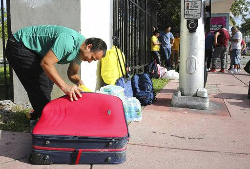 Leonel Geronimo, stuffs food into his suitcase as he and others wait for a bus in anticipation of Hurricane Irma in Miami Beach, Fla., Friday, Sept. 8, 2017. Geronimo wants to get to a shelter off the beach, but is not sure what bus to take or which shelter to go.