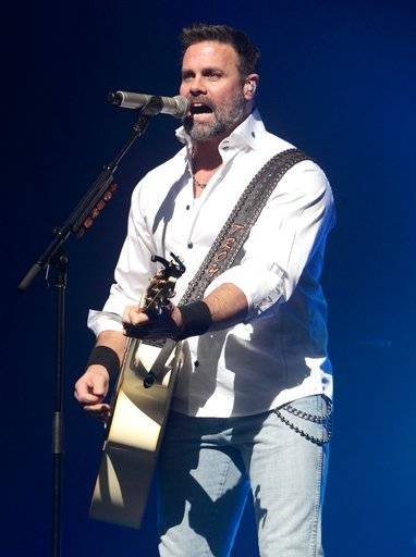 FILE - In this Jan. 17, 2013 file photo, Troy Gentry of the Country Music duo Montgomery Gentry performs on the Rebels On The Run Tour in Lancaster, Pa. Gentry, one half of the award-winning country music duo Montgomery Gentry, died Friday, Sept. 8, 2017, in a helicopter crash, according to a statement from the band's website. He was 50. The group was supposed to perform Friday at the Flying W Airport & Resort in Medford, N.J. (Photo by Owen Sweeney/Invision/AP, File)