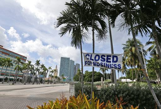 "A ""Closed For Business,"" sign is strung across palm trees outside Bayside Marketplace in downtown Miami, Friday, Sept. 8, 2017. Hurricane Irma aimed its sights on millions of homes and businesses in Florida and officials warned that time was running out to evacuate ahead of the deadly hurricane, which was headed Friday on a long-feared path right through the heart of the peninsula. (AP Photo/Wilfredo Lee)"