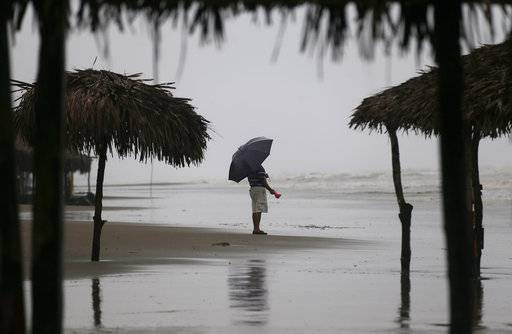 A man stands on the shore under an overcast sky before the arrival of Hurricane Katia, in Tecolutla, Veracruz state, Mexico, Friday, Sept. 8, 2017. The U.S. National Hurricane Center said Katia was likely to strike the Gulf coast in the state of Veracruz early Saturday as a Category 2 storm that could bring life-threatening floods. (AP Photo/Eduardo Verdugo)