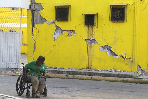 A man sits in his wheelchair backdropped by a building damaged in a massive earthquake, in Juchitan, Oaxaca state, Mexico Friday, Sept. 8, 2017. One of the most powerful earthquakes ever to strike Mexico has hit off its southern Pacific coast, killing at least 32 people, toppling houses, government offices and businesses. (AP Photo/Luis Alberto Cruz)