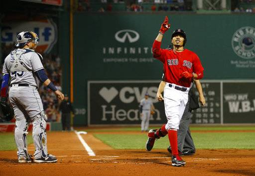 Boston Red Sox's Mookie Betts points skyward after hitting a three-run home run as Tampa Bay Rays catcher Jesus Sucre watches during the first inning of a baseball game at Fenway Park in Boston, Friday, Sept. 8, 2017. (AP Photo/Winslow Townson)
