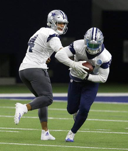 Dallas Cowboys quarterback Dak Prescott (4) hands off to teammate running back Ezekiel Elliott (21) during an NFL football practice in Frisco, Texas, Thursday, Sept. 7, 2017. (AP Photo/LM Otero)