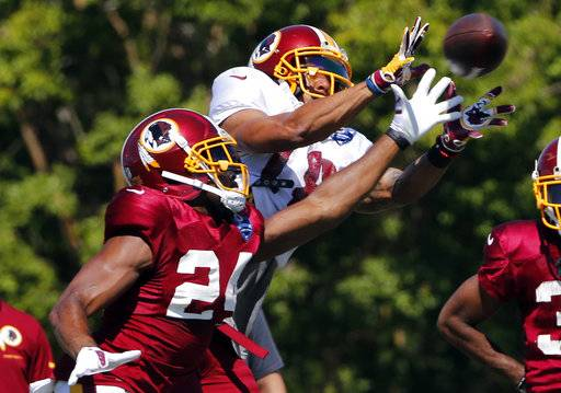 FILE - In this July 31, 2017, file photo, Washington Redskins wide receiver Josh Doctson (18) hauls in a pass in front of cornerback Josh Norman (24) during practice at the Washington Redskins NFL training camp in Richmond,. Va. Doctson is ready to play and eager to show the Redskins why they drafted him in the first round. (AP Photo/Steve Helber, File)