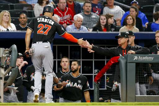 Miami Marlins' Giancarlo Stanton (27) high-fives manager Don Mattingly after scoring in the seventh inning of a baseball game against the Atlanta Braves, Thursday, Sept. 7, 2017, in Atlanta. (AP Photo/Brett Davis)