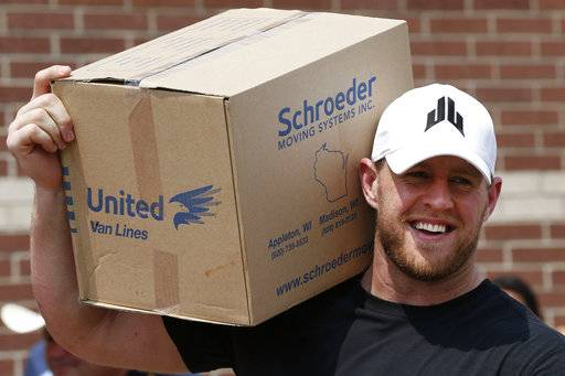 FILE - In this Sept. 3, 2017, file photo, Houston Texans defensive end J.J. Watt holds a box of relief supplies on his shoulder while handing them out to people impacted by Hurricane Harvey in Houston. Watt is being honored by the NFL Players Association after raising more than $29 million for Hurricane Harvey relief efforts. (Brett Coomer/Houston Chronicle via AP, Pool)