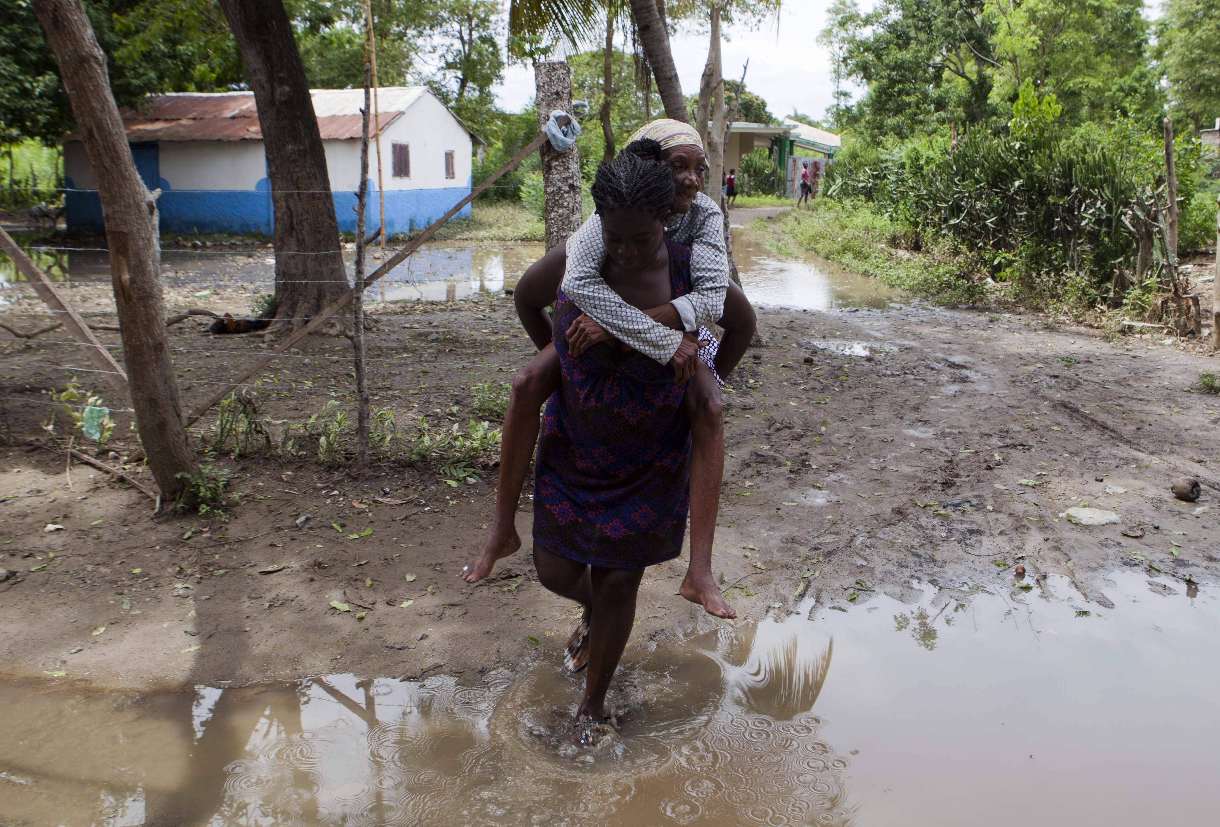 A woman carries her grandmother away from a flooded home after Hurricane Irma passed through Haiti on its way to Florida.