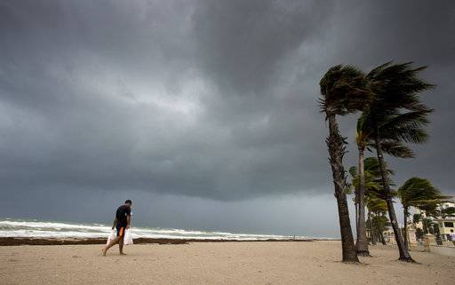 A man walks along the beach with heavy winds and threatening skies in Hollywood, Fla., as Hurricane Irma approaches the state on Saturday, Sept. 9, 2017. (Paul Chiasson/The Canadian Press via AP)