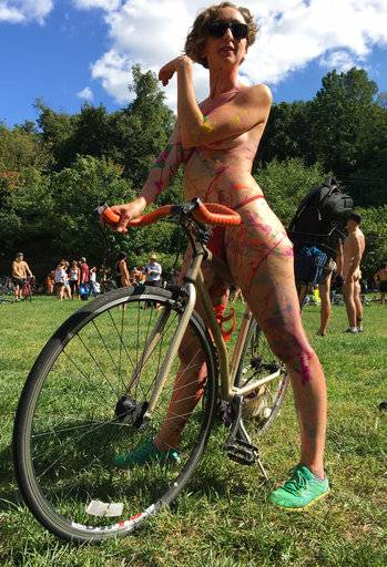 Olivia Neely, a topless cyclist wearing body paint, motions before the start of the annual Philly Naked Bike Ride in Philadelphia on Saturday Sept. 9, 2017. (AP Photo/Dino Hazell)