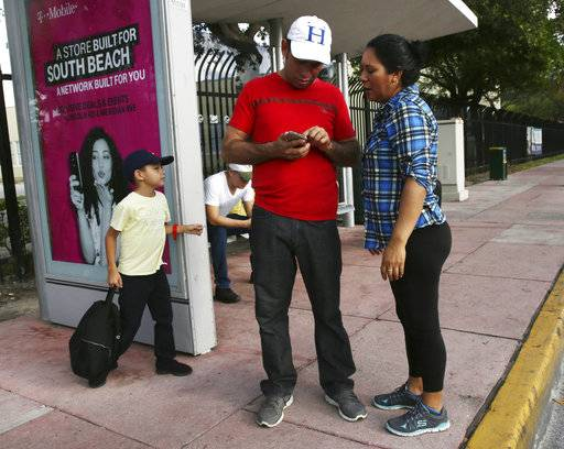 Wilman Hernandez and his wife Brenda Ramirez, check their phones for the location of shelters and their capacity while waiting for a bus in Miami Beach, Fla., Friday, Sept. 9, 2017. The main hub leading Floridians out of Hurricane Irma's path is bumper to bumper with those who can afford to escape. As Hurricane Irma threatened South's Beach's elite, some booked pricey airline seats, chartered private planes and found fancy hotels like a forced vacation. But many, including the low-wage workers in Florida's tourism industry, couldn't afford to stock up on supplies and struggled to find their way to shelters. (AP Photo/Marta Lavandier)