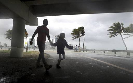 The winds and sea are whipped up off of the Rickenbacker Causeway as two people cross the street in Miami as Hurricane Irma approaches on Saturday, Sept. 9, 2017. ( Mike Stocker/South Florida Sun-Sentinel via AP)
