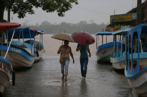 Residents walk past boats that were moved on land in preparation for the expected arrival of Hurricane Katia, in Tecolutla, Veracruz state, Mexico, Friday, Sept. 8, 2017. Hurricane Katia in the Gulf of Mexico is stationary north-northeast of Veracruz and forecasters didn't expect much movement overnight. (AP Photo/Eduardo Verdugo)